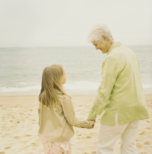 浜辺で手を繋ぐ祖母と孫娘の写真素材 [FYI03953701]