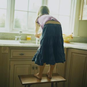 キッチンで手を洗う少女の後姿の写真素材 [FYI03953705]
