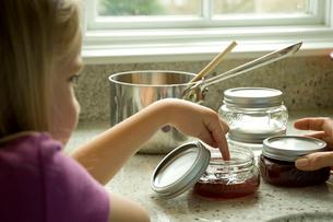 料理中につまみ食いをする少女の写真素材 [FYI03953717]