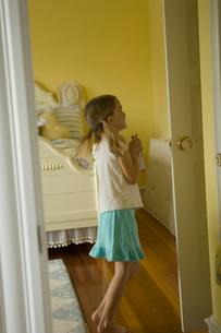 部屋のクローゼットの中を見ている少女の写真素材 [FYI03953732]
