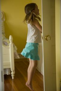 部屋のクローゼットの中を見ている少女の写真素材 [FYI03953736]