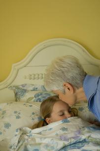 ベッドで孫娘を寝かしつける祖母の写真素材 [FYI03953738]