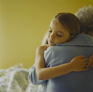 寝る前に抱き合う孫娘と祖母の写真素材 [FYI03953740]
