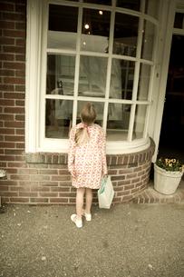 お店のウィンドーを覗いている少女の写真素材 [FYI03953746]
