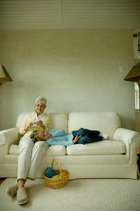 編み物をする祖母の膝に寝る孫娘の写真素材 [FYI03953765]