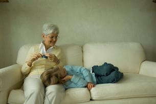 編み物をする祖母の膝に寝る孫娘の写真素材 [FYI03953767]