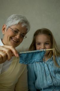 孫娘に編み物を見せる祖母の写真素材 [FYI03953768]