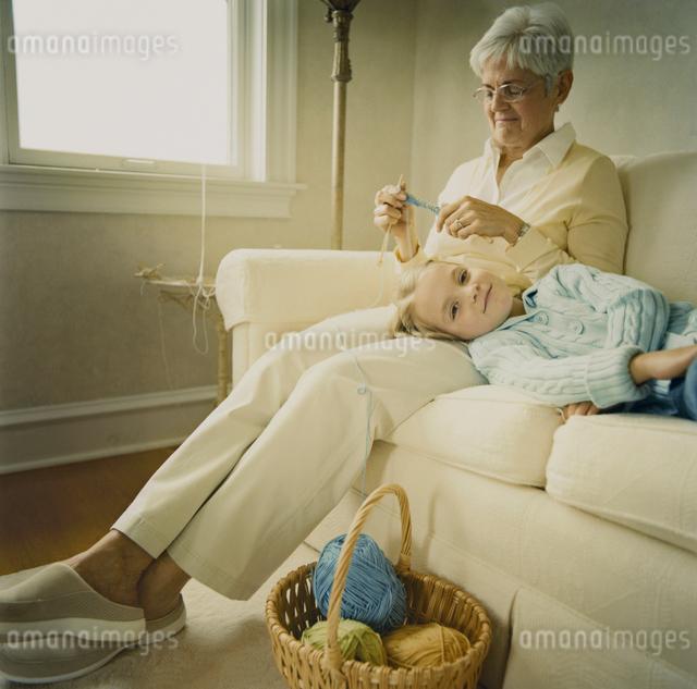 編み物をする祖母の膝に寝る孫娘の写真素材 [FYI03953771]