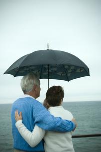 傘をさし海を眺めるシニアカップルの後ろ姿の写真素材 [FYI03953815]