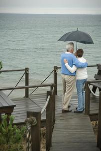 傘をさし海を眺めるシニアカップルの後ろ姿の写真素材 [FYI03953817]