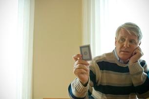 トランプのカードを見せるシニア男性の写真素材 [FYI03953820]