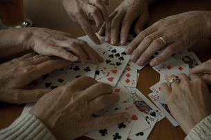 トランプのカードをシャッフルする4人の手元の写真素材 [FYI03953821]