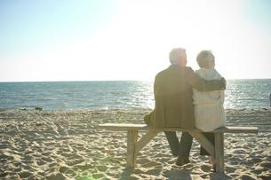 砂浜でベンチに座るシニアカップルの写真素材 [FYI03953847]
