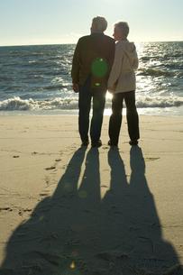 砂浜に佇むシニアカップルの後ろ姿の写真素材 [FYI03953850]