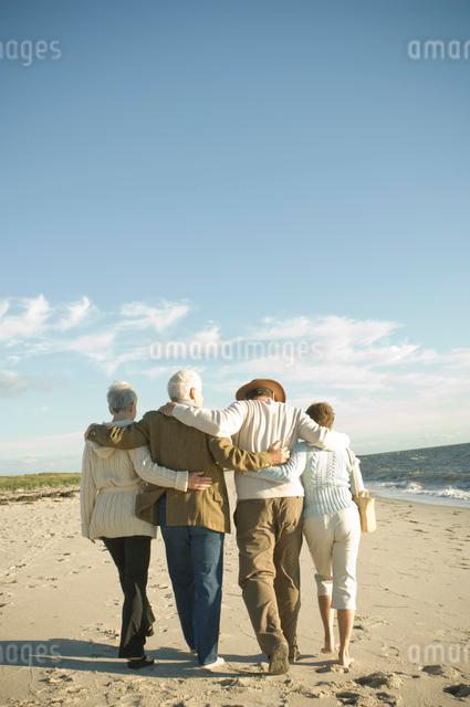 肩を組んで浜辺を歩くシニアカップル2組の写真素材 [FYI03953856]