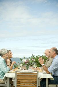 海辺のテラスで食事を楽しむシニアカップル2組の写真素材 [FYI03953874]