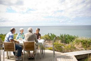 海辺のテラスで食事を楽しむシニアカップル2組の写真素材 [FYI03953880]