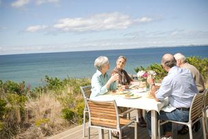 海辺のテラスで食事を楽しむシニアカップル2組の写真素材 [FYI03953885]