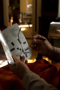 クロスワードパズルをするシニア男性の手元の写真素材 [FYI03953895]