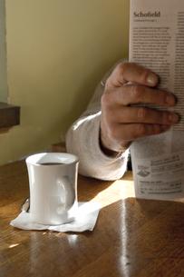 新聞を読むシニア男性の手元とコーヒーカップの写真素材 [FYI03953917]