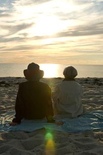 浜辺に座り海を見つめるシニアカップルの写真素材 [FYI03953941]