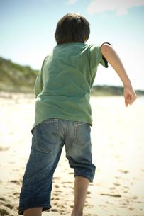 砂浜を走る少年の後ろ姿の写真素材 [FYI03953978]