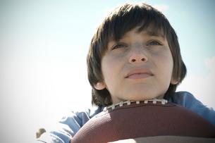 あごをフットボールに乗せる少年の写真素材 [FYI03953986]