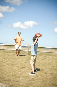 フットボールで遊ぶ父と息子の写真素材 [FYI03953988]