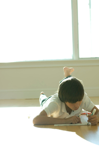 床に寝そべりお絵かきをする少年の写真素材 [FYI03954009]