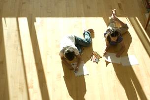 床に寝そべりお絵かきをする少年と少女の写真素材 [FYI03954012]