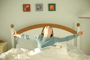 ベッドから起き上がる少年の写真素材 [FYI03954018]
