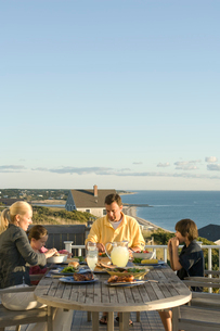 テラスで食卓を囲む家族4人の写真素材 [FYI03954022]