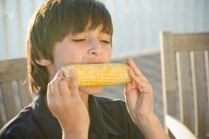 とうもろこしを食べる少年の写真素材 [FYI03954024]