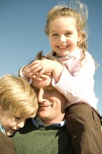肩車をしてじゃれ合う家族3人の写真素材 [FYI03954115]