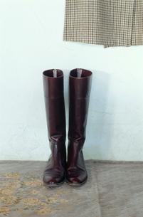 床に置かれたブーツと壁にかかったコートの写真素材 [FYI03954238]
