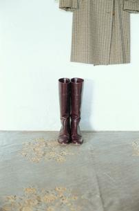床に置かれたブーツと壁にかかったコートの写真素材 [FYI03954239]