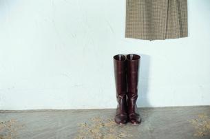 床に置かれたブーツと壁にかかったコートの写真素材 [FYI03954240]