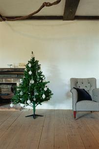 暖炉脇にあるクリスマスツリーと椅子の写真素材 [FYI03954272]