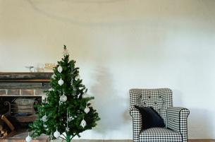 暖炉脇にあるクリスマスツリーと椅子の写真素材 [FYI03954274]