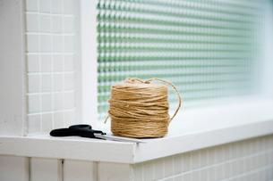 窓際に置かれた紐とハサミの写真素材 [FYI03954366]