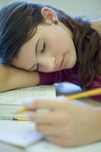 教室で昼寝している女子学生の写真素材 [FYI03954411]
