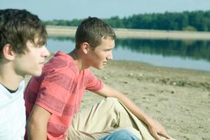 湖畔で座る男子学生2人の写真素材 [FYI03954424]