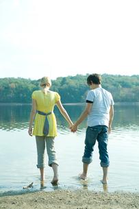 手をつなぎ湖畔にはいる男女の写真素材 [FYI03954426]