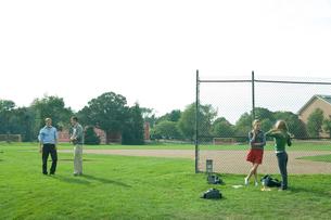芝生の運動場で戯れる学生達の写真素材 [FYI03954504]