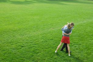 芝生で抱き合う男女学生の写真素材 [FYI03954516]