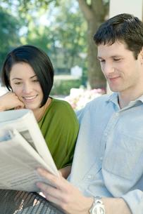 新聞を一緒に眺めるカップルの写真素材 [FYI03954529]