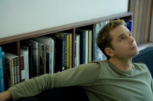 ソファに座り上を見る男性の写真素材 [FYI03954542]