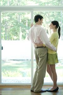 窓際で抱き合うカップルの写真素材 [FYI03954549]