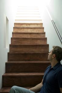 階段に座り上を見上げる男性の写真素材 [FYI03954555]