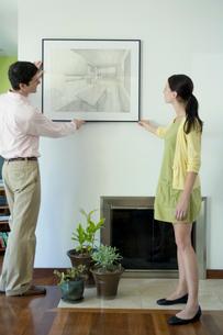 壁に絵を飾るカップルの写真素材 [FYI03954556]